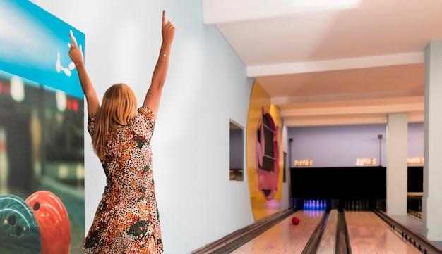 Vista posteriore donna che gioca a bowling