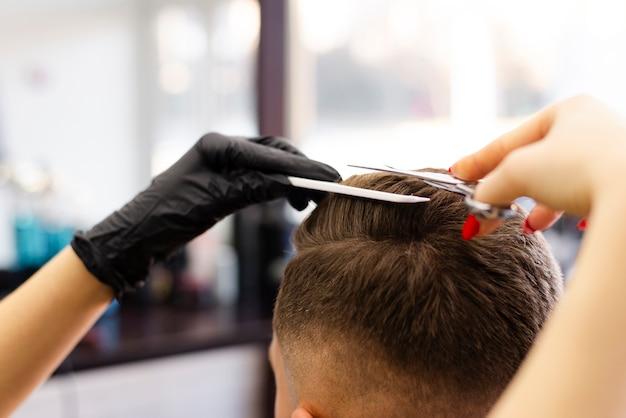 Vista posteriore donna che taglia i capelli del suo cliente