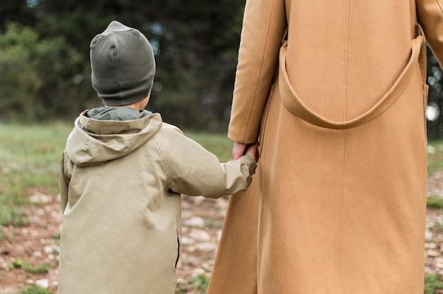 Vista posteriore donna che tiene il suo bambino per mano