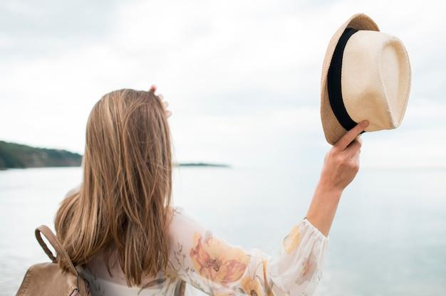 Vista posteriore donna con cappello vacanza