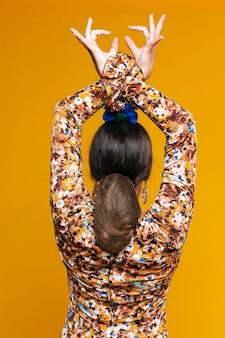 Vista posteriore donna flamenca alzando le mani