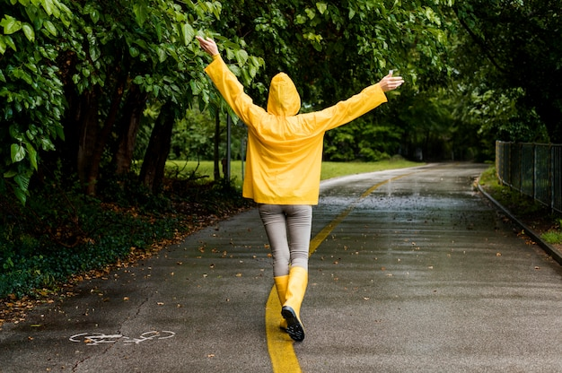 Vista posteriore donna in cappotto di pioggia