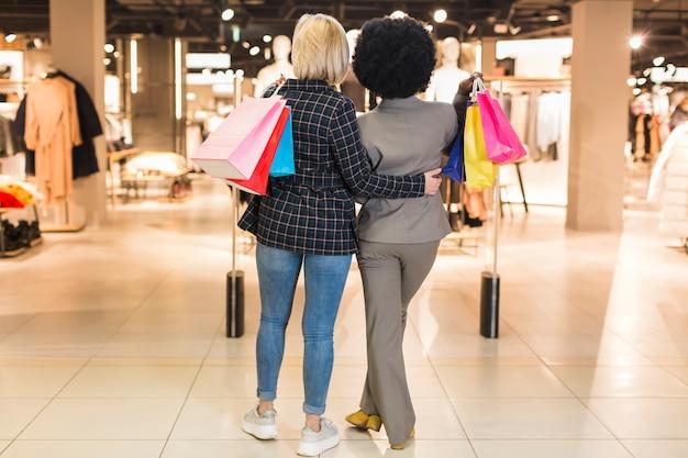 Vista posteriore donne al centro commerciale insieme