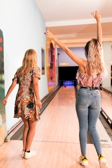 Vista posteriore donne che giocano a bowling