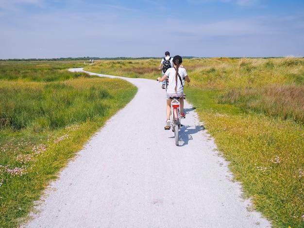Vista posteriore famiglia di ciclisti che viaggiano su strada nella zona delle dune dell'isola di schiermonnikoog.