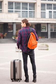 Vista posteriore giovane turista con bagagli