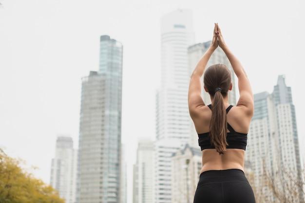 Vista posteriore in forma donna alzando le braccia
