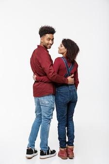 Vista posteriore integrale di giovani coppie dell'afroamericano che abbracciano insieme