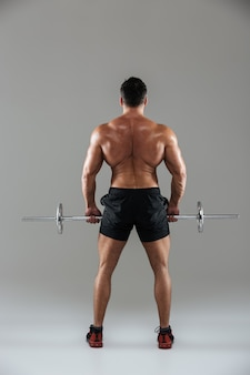 Vista posteriore integrale di un bodybuilder maschio senza camicia muscolare
