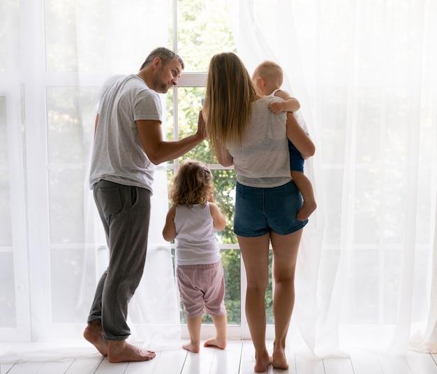 Vista posteriore membri della famiglia guardando fuori dalla finestra