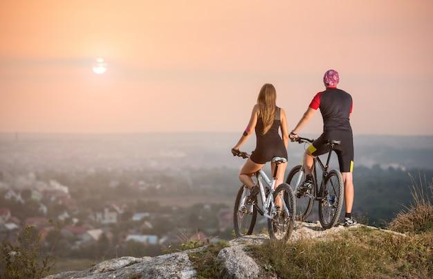 Vista posteriore motociclisti maschili e femminili con moutains biciclette in piedi sulla cima di una collina