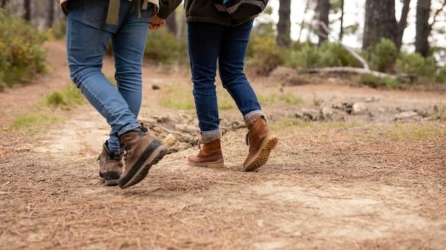 Vista posteriore persone con stivali a piedi