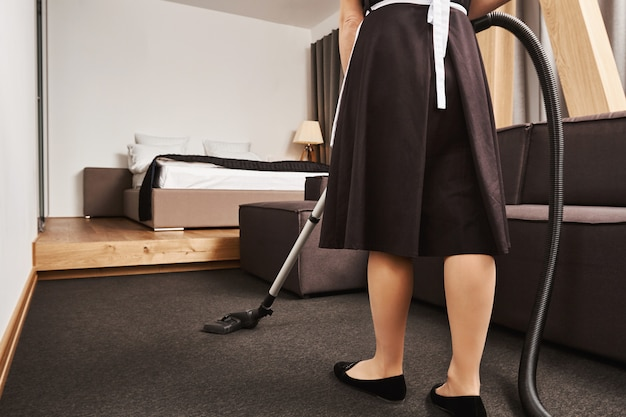 Vista posteriore ritagliata della cameriera femminile che pulisce il pavimento del soggiorno con l'aspirapolvere, essendo occupata e in fretta per finire prima che il proprietario tornerà a casa, cercando di rimuovere tutto lo sporco e rendere pulito l'appartamento
