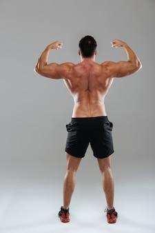Vista posteriore ritratto a figura intera di un forte bodybuilder maschio