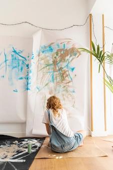 Vista posteriore seduta donna pittura