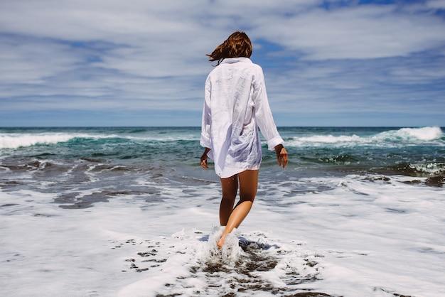 Vista posteriore sulle donne con bei capelli castani in camicia bianca sulla spiaggia