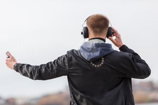 Vista posteriore uomo che ascolta la musica all'aperto