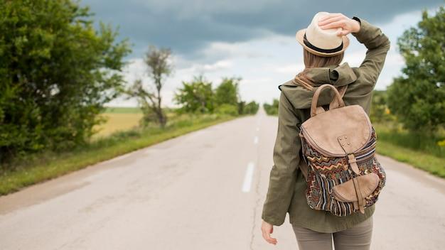 Vista posteriore viaggiatore con cappello in attesa di un passaggio