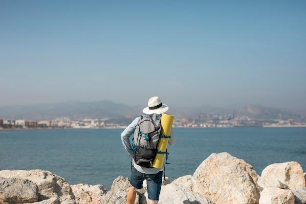 Vista posteriore viaggiatore in riva al mare