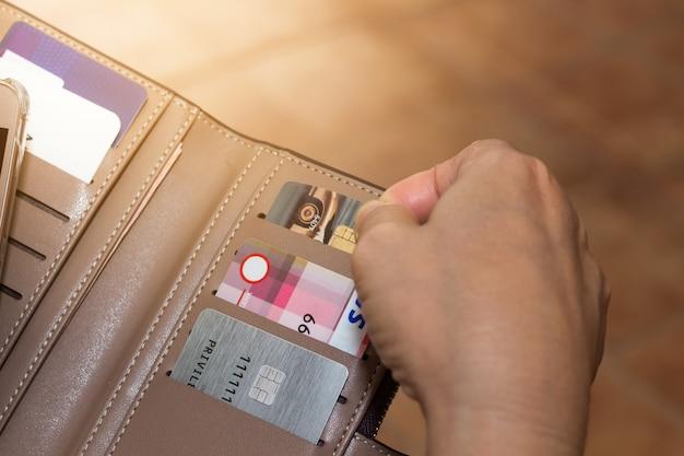 Vista potata del colpo delle mani femminili che selezionano le carte di credito dal suo portafoglio