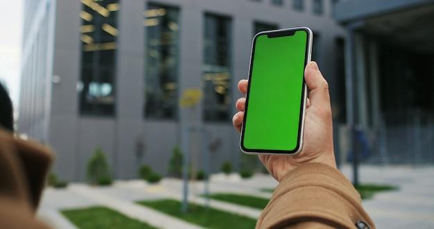 Vista potata del colpo dello smart phone maschio della tenuta della mano sopra sul fondo della via della città con lo schermo in bianco dello spazio della copia per il vostro messaggio di testo o contenuto informativo