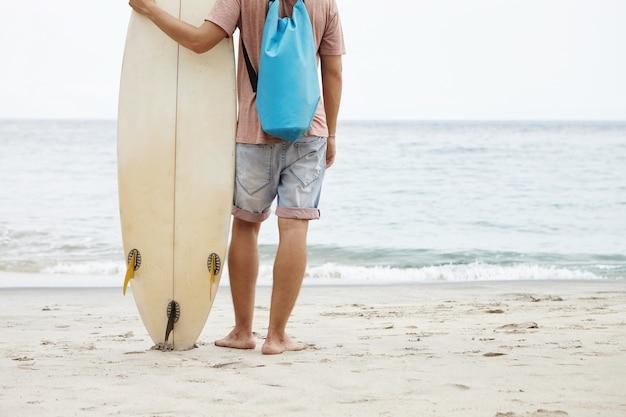 Vista potata del giovane con lo zaino blu che sta sulla spiaggia sabbiosa e che esamina l'acqua di mare blu