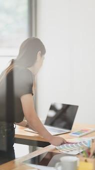 Vista potata del grafico femminile che lavora al suo progetto