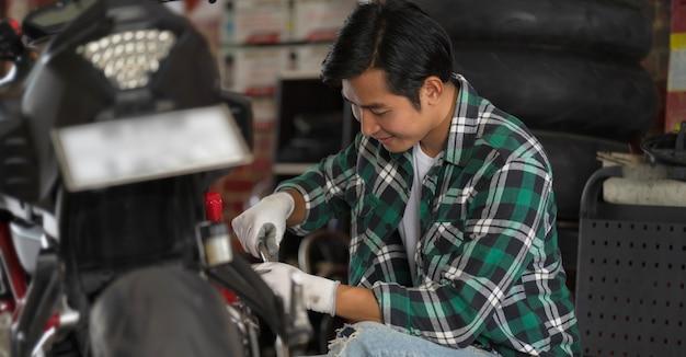 Vista potata del meccanico di motocicletta utilizzando una chiave inglese e una presa su una moto