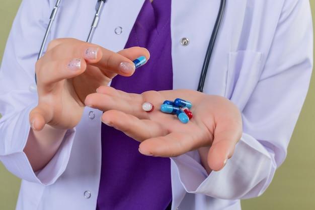 Vista potata del medico della donna in camice bianco che tiene le pillole nelle mani sul verde