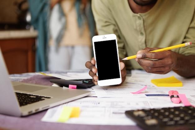 Vista potata dell'uomo afroamericano casuale che indica la matita allo schermo in bianco del telefono cellulare