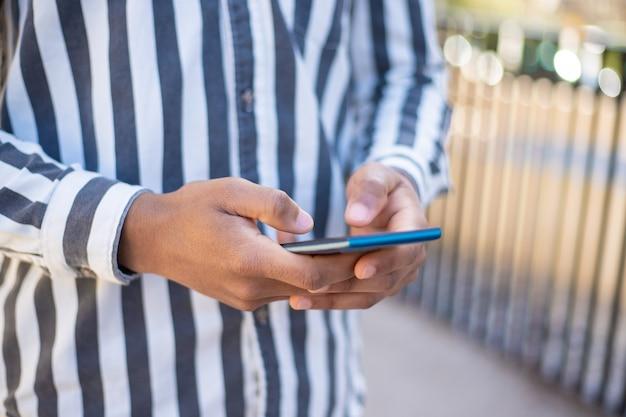 Vista potata dell'uomo che manda un sms sullo smartphone