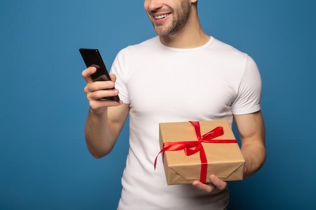 Vista potata dell'uomo che per mezzo dello smartphone e tenendo il contenitore di regalo isolato sul blu