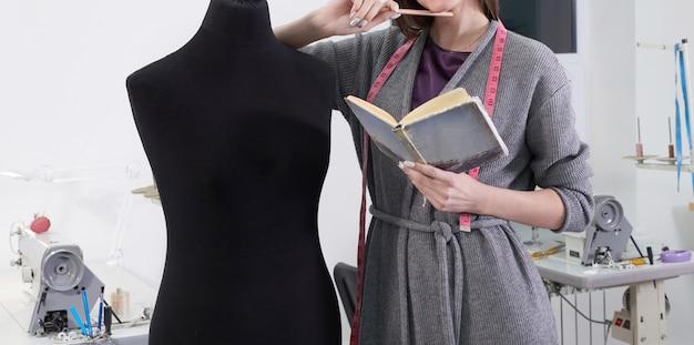 Vista potata della cucitrice che misura manichino nero in officina, lavoro dello studio del sarto