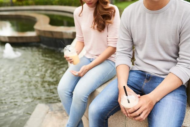 Vista potata delle coppie irriconoscibili che godono dei cocktail nel parco
