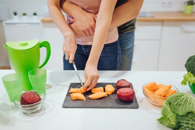 Vista potata delle mani della donna che tagliano le verdure organiche. famiglia amante del vegano che cucina le verdure nella cucina.
