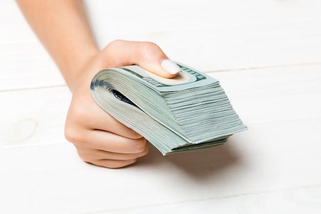 Vista prospettica della mano femminile in possesso di un pacco di soldi