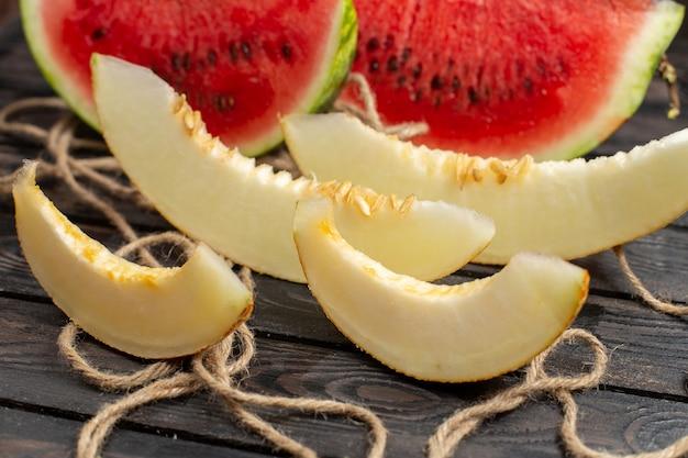Vista ravvicinata anteriore affettata frutta dolce tagliata a metà anguria fresca con melone sullo sfondo rustico marrone