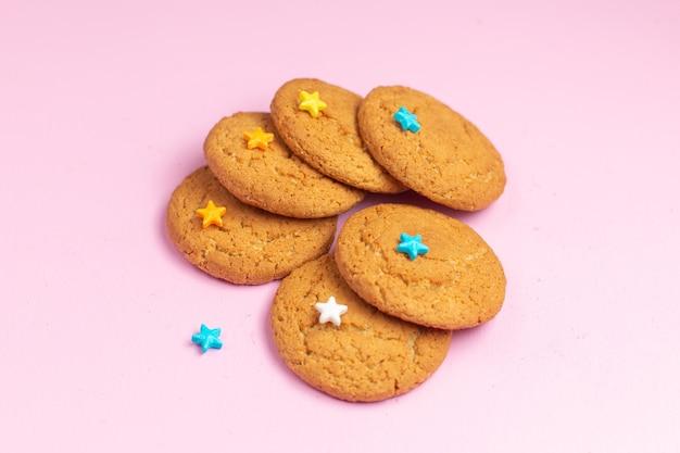 Vista ravvicinata anteriore deliziosi biscotti dolci al forno rivestiti sullo sfondo rosa zucchero dolce biscotto cuocere il tè