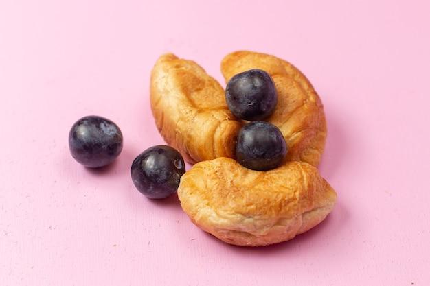 Vista ravvicinata anteriore deliziosi croissant al forno con ripieno di frutta insieme a prugnoli su sfondo rosa pasticceria cuocere