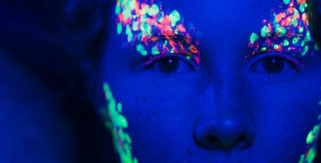 Vista ravvicinata degli occhi delle donne e trucco fluorescente