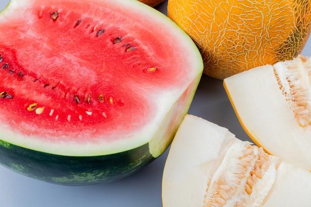 Vista ravvicinata del modello di taglio e frutti interi come anguria e melone su sfondo grigio bluastro