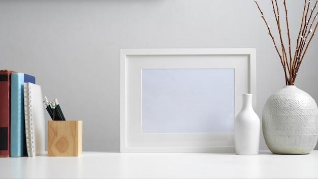 Vista ravvicinata del piano di lavoro con libri, cancelleria, mock up frame, decorazioni e copia spazio in ufficio a casa