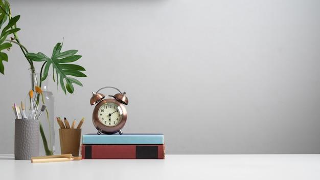 Vista ravvicinata del piano di lavoro con libri, cancelleria, strumenti di pittura, orologio, vaso per piante e copia spazio in ufficio a casa