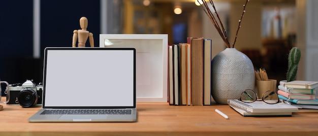 Vista ravvicinata del posto di lavoro con laptop schermo vuoto, libri, forniture e decorazioni sulla scrivania in legno nella stanza dell'ufficio