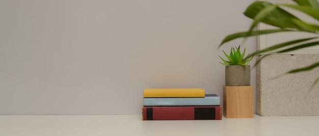 Vista ravvicinata del semplice tavolo da studio con copia spazio, libri, vaso di piante e decorazioni sul tavolo bianco