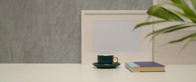 Vista ravvicinata del tavolo da lavoro con tazza, libro, mock up frame, vaso per piante e copia spazio nel soggiorno