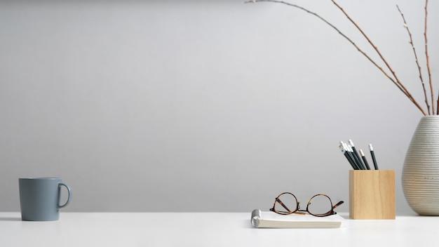 Vista ravvicinata del tavolo di studio con cancelleria, occhiali da vista, taccuino, tazza, decorazione e copia spazio in ufficio a casa