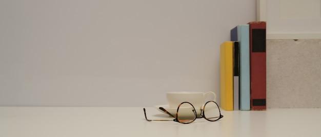 Vista ravvicinata del tavolo di studio con occhiali, libri, tazza, decorazioni e copia spazio sul tavolo bianco