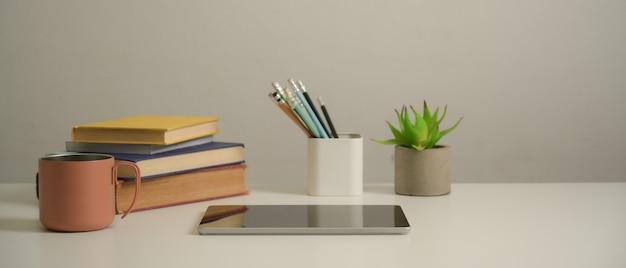Vista ravvicinata del tavolo di studio con tavoletta digitale, libri, cancelleria, tazza e decorazioni in soggiorno