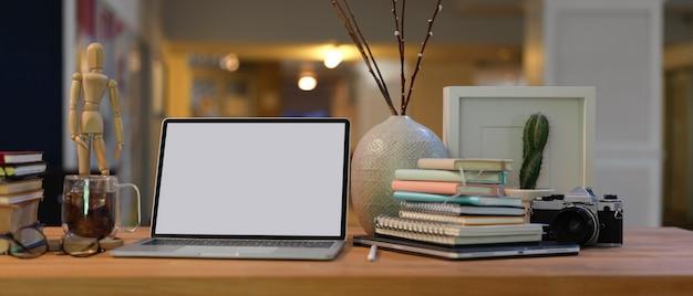Vista ravvicinata dell'area di lavoro con laptop schermo vuoto, libri, forniture e decorazioni sulla scrivania in legno nel soggiorno